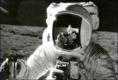 This is a photograph of Alan Bean on the moon holding up a sample he just collected.